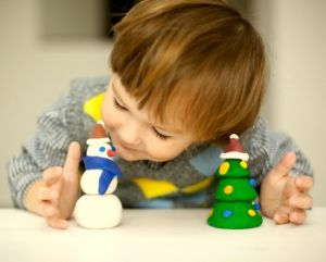 Young boy playing with a clay snowman and a clay tree.